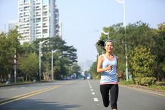 Fitness woman running at city street Stock Images