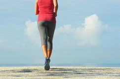Fitness woman running in coast at sunrise. Young woman runner jogging during outdoors workout on beach. Concept healthy workout exercise athlete stock photography
