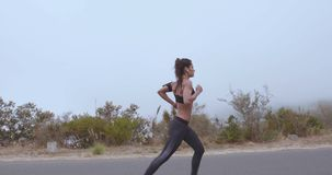 Fitness woman running on country road in foggy morning stock video