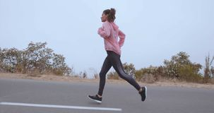 Fitness woman running on countryside road stock video
