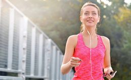 Fitness woman running. Woman jogging on urban road and listen music. Fitness girl training outdoor Stock Images