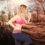 Fitness woman running in forest location Royalty Free Stock Photo