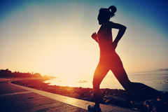 Fitness woman running at forest trail Stock Photos