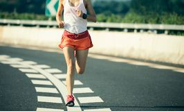 fitness woman running on highway road stock images
