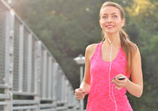Fitness woman running. Woman jogging on urban road and listen music. Fitness girl training outdoor Stock Photos