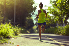Fitness woman running on morning tropical forest trail Stock Photo