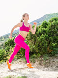 Fitness woman running in nature. Sporty slim girl in mountains. Stock Photos