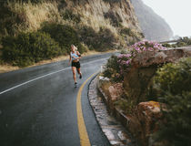Fitness woman running outdoors on highway. Full length shot of fitness woman running outdoors on highway in countryside. Female athlete sprinting on road royalty free stock photos