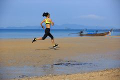 Fitness woman running on sandy beach. Young fitness woman running on sandy beach stock photography