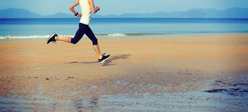 Fitness woman running on sandy beach. Young fitness woman running on sunrise sandy beach royalty free stock images