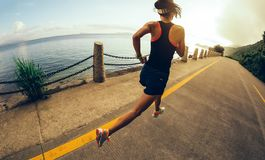 Woman running on seaside trail stock photos