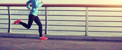 Fitness woman running on seaside royalty free stock photos