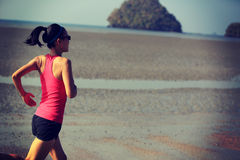 Fitness woman running at sunrise beach Royalty Free Stock Images