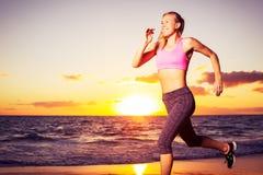 Fitness woman running at sunset Stock Photo