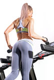 Fitness woman running on treadmill in gym Stock Images