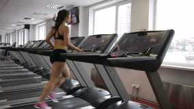 Fitness woman running on treadmill at gym indoors. She jogging along rotating belt of machine, holds on to handrail then stops and takes bottle of water stock footage
