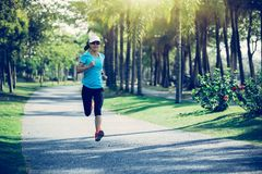 Fitness woman running at tropical park Royalty Free Stock Images