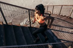 Woman running up the stairway along the beach. Fitness woman running up the stairway along the beach. Female athlete exercising outdoors in morning Stock Image