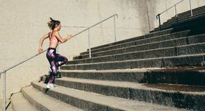 Fitness woman running up on steps Stock Photos