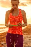 Fitness woman on seashore with headphones listening to music. Refreshing wild sea side workout. healthy fitness woman in sports gear on the seashore with Stock Images