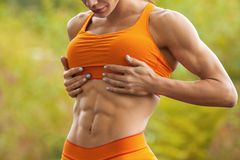 Fitness woman showing abs and flat belly. Athletic girl outdoors, shaped abdominal, slim waist Stock Image