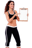 Fitness woman showing a blank clip board Royalty Free Stock Photos
