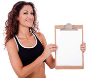 Fitness woman showing a blank clip board Royalty Free Stock Photo