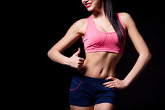 Fitness woman showing thumbs up success sign standing  isolated on black background. Healthy lifestyle concept Royalty Free Stock Image