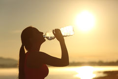 Fitness woman silhouette drinking water from a bottle. Profile of a fitness woman silhouette drinking water from a bottle at sunset with the sun in the stock images
