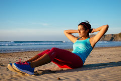 Fitness woman sit ups exercising. Fitness woman doing sit ups exercising on beach. Sporty girl workout outdoors on summer Stock Photography