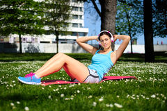 Fitness woman on sit ups workout. Fit woman working out doing sit ups fitness exercises in city park on spring or summer. Beautiful fitness girl during crunches Royalty Free Stock Photo