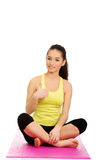Fitness woman sitting on exercise mat. Royalty Free Stock Image