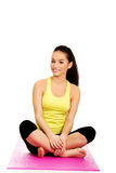 Fitness woman sitting on exercise mat. Stock Photography
