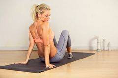 Fitness Woman Sitting on a Mat Royalty Free Stock Images
