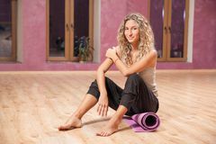 Fitness woman sitting on mat indoor royalty free stock photos