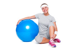 Fitness woman sitting near blue ball Stock Photo