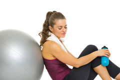 Fitness woman sitting near fitness ball with bottle of water Royalty Free Stock Photos