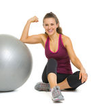 Fitness woman sitting near fitness ball and showing biceps Stock Images