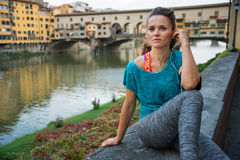 Fitness woman sitting near ponte vecchio in florence, italy and Stock Photography