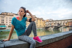 Fitness woman sitting near ponte vecchio in italy Royalty Free Stock Image