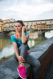 Fitness woman sitting near ponte vecchio in italy Stock Photo