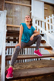 Fitness woman sitting on stairs of beach house Stock Photo