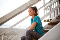 Fitness woman sitting on stairs of beach house Stock Photography