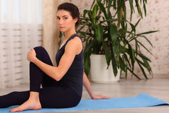 Fitness woman sitting in yoga pose at home. Female in sportswear doing meditation on exercise on mat in her apartment. Stock Images