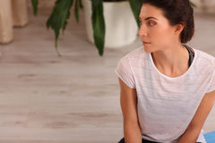 Fitness woman sitting in yoga pose at home. Female in sportswear doing meditation on exercise on mat in living room of her apartme Royalty Free Stock Photography