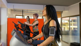 Fitness woman with smartphone arm strap listening to music and doing sport activity. On the treadmill stock footage