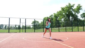 Fitness woman in sportswear doing various exercises on an orange basketball field with white markings, at the stadium