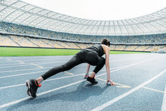 Fitness woman in sportswear in starting position on stadium Royalty Free Stock Image