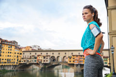 Fitness woman in sportswear staying next to Ponte Vecchio bridge Stock Photo