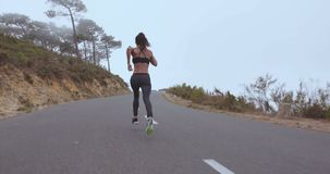 Fitness woman sprinting on countryside highway stock video footage